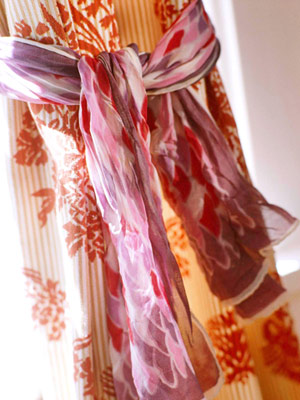 Use small scarves to tie back curtains.  Source