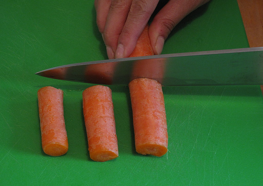 Use a larger kitchen knife to chop your vegetable (shown here, a carrot, scrubbed clean), into two-inch pieces.