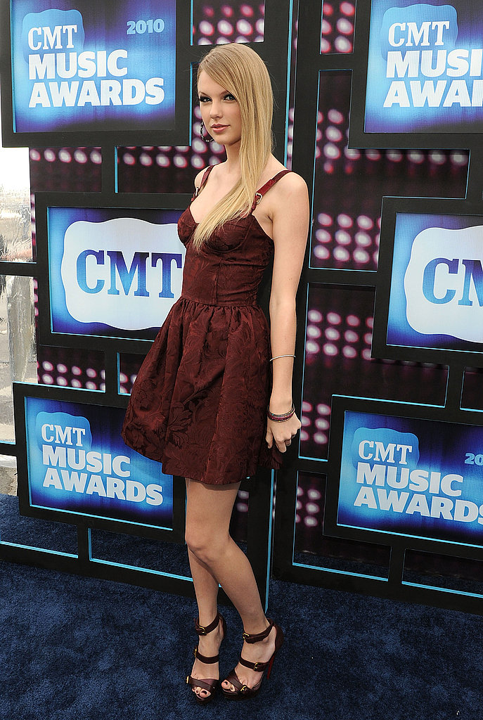 Taylor Swift in deep burgundy John Galliano — interesting color on her.