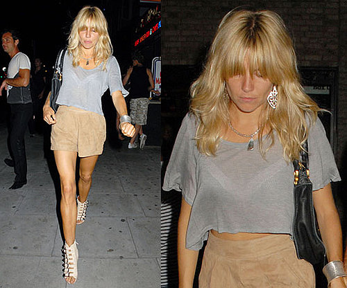 Sienna Miller Wearing Tan Suede Shorts, Gray Cropped Tee, and Buckle Wedges