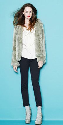 The white shirt and black pants are crisp, but the faux fur coat adds a dash of cozy chic.