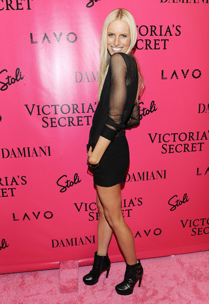 Flaunting a pair of legs for days in short black shorts and sheer on top — it's incredibly cool Karolina, post-VS runway.