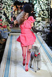 Anna Dello Russo strutting her pink stuff with a dog.