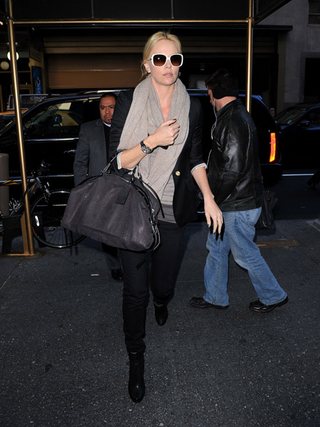 Charlize Theron in NYC — digging the white shades contrasted by the moody ensemble.