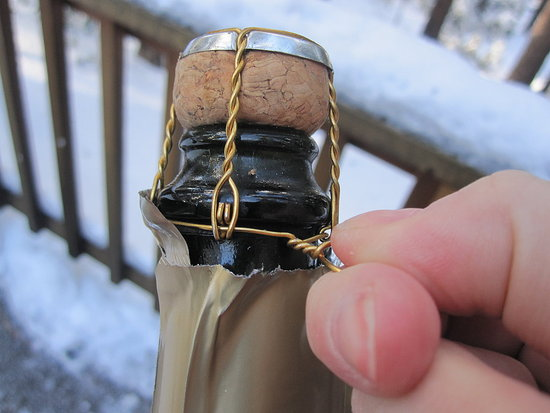 Untwist the cage. Every bottle of sparkling wine that's made with classic méthode champenoise is closed shut with a wire cage; it requires six twists to remove it. Discard the cage.