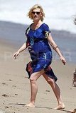 January Jones walks on the sand.