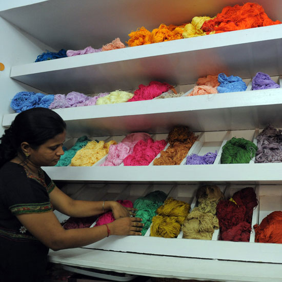 An Indian woman organizes threads by color.