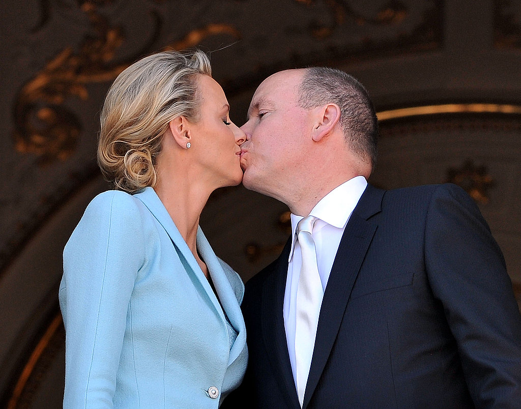 Princess Charlene of Monaco and Prince Albert II of Monaco kiss on the balcony.