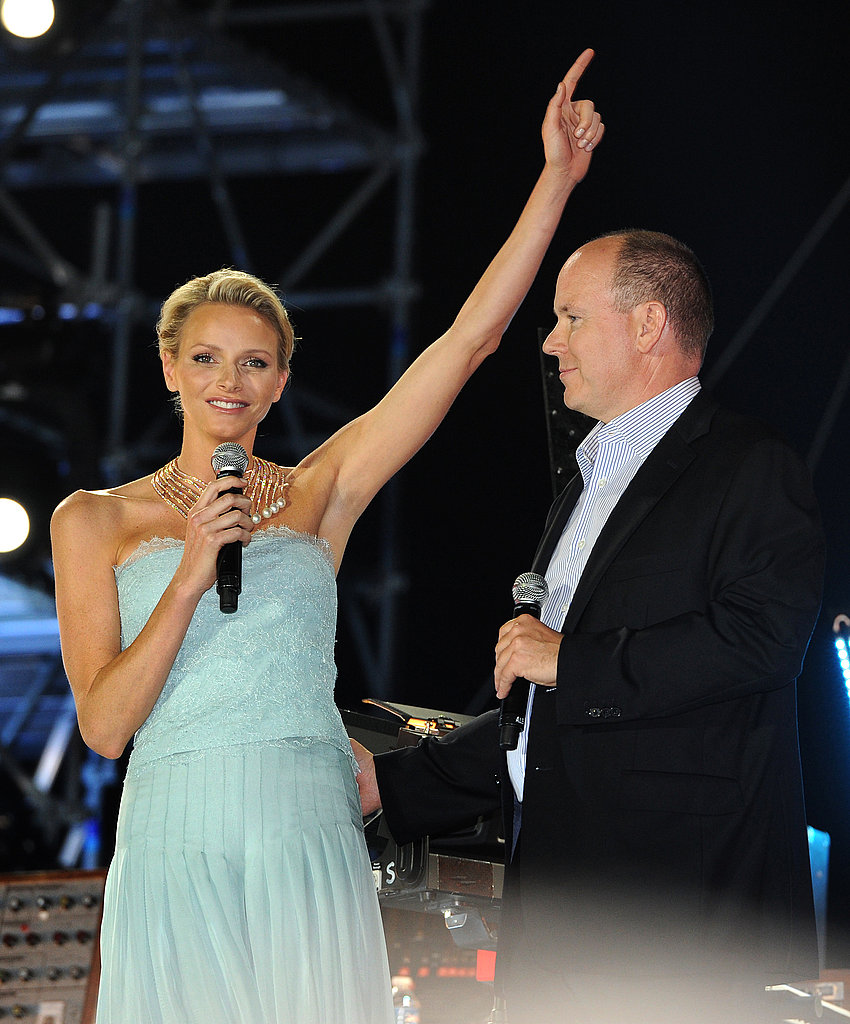 Princess Charlene of Monaco raises her hand while on stage with Prince Albert II of Monaco.