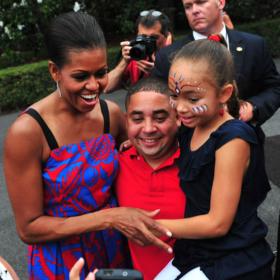 First Lady Michelle Obama hugs guests of the White House's Independence Day BBQ honoring armed servicemen and women.