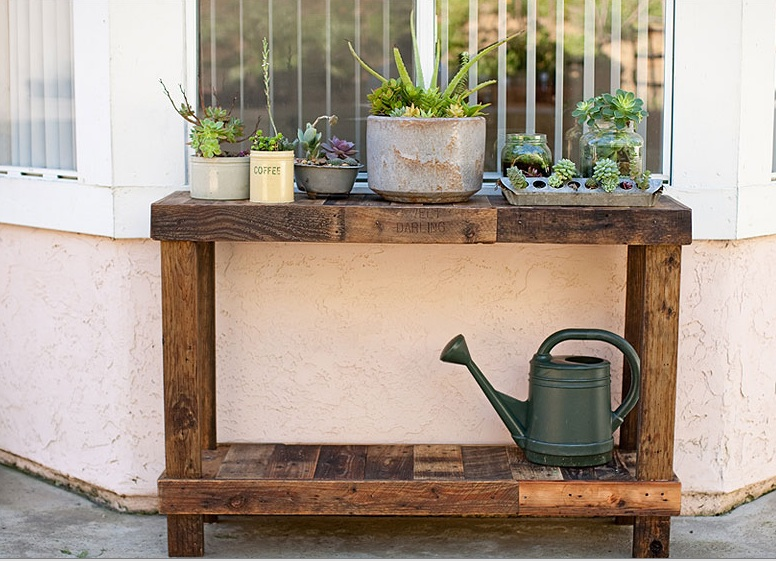 A collection of succulents on a handmade palette table look lovely when displayed in crockery and vintage metal vessels. Find out how to make a side table like this here.