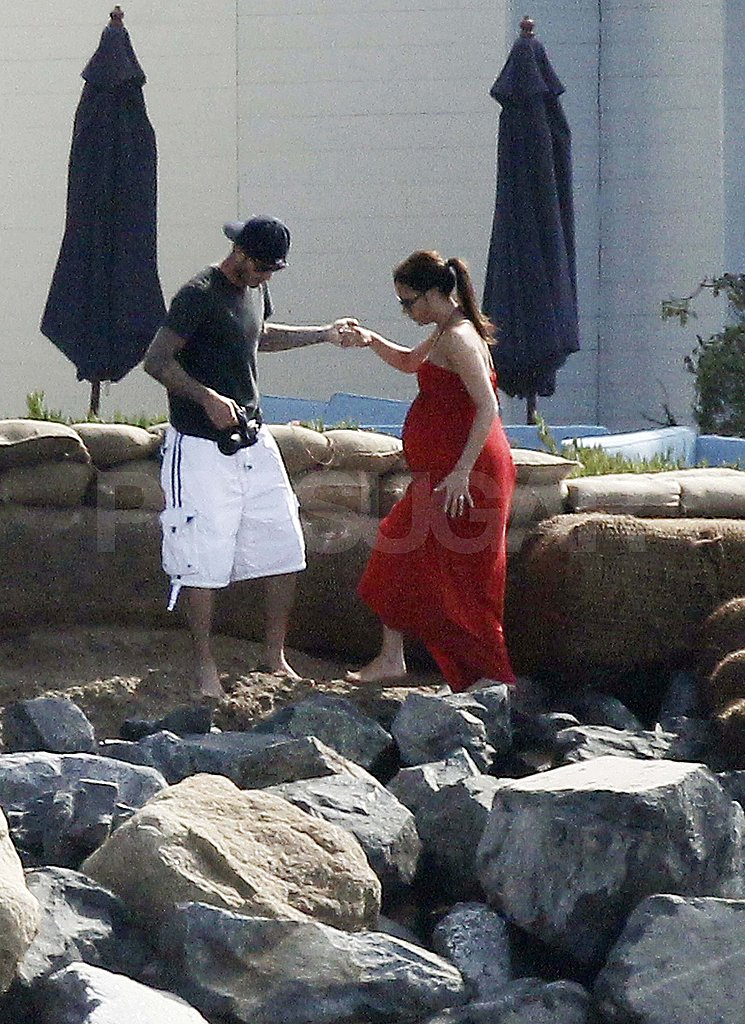 Victoria Beckham pregnant in a red dress with David.