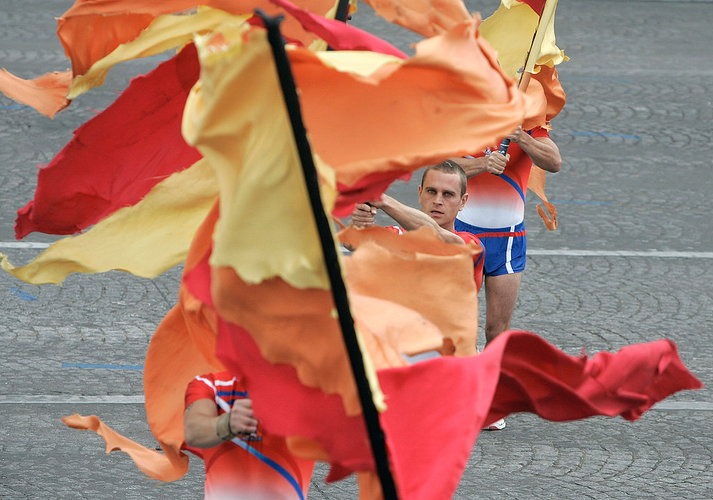 During the annual Bastille Day parade, Parisian firemen perform with flags.