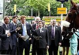 Prince Harry talks to horse race officials.