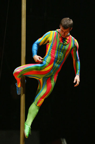 A Cirque du Soleil performer balances on a pole.