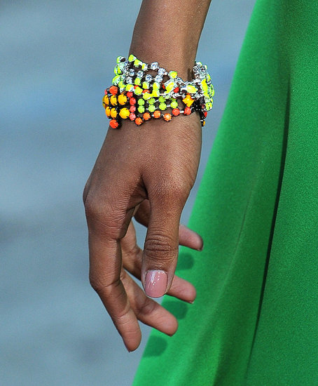 A close-up of Freida wearing Tom Binns neon bracelets.
