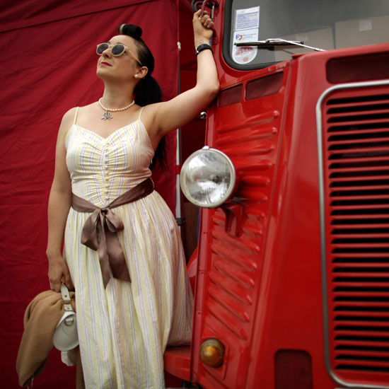 A woman poses next to a red truck at the Vintage Festival.