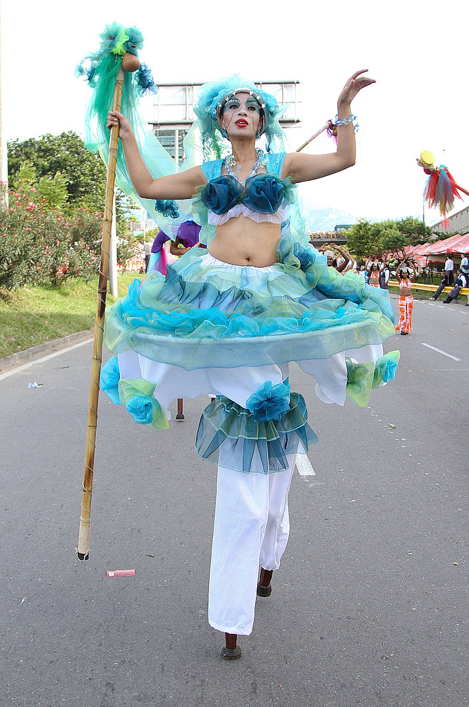 A woman on stilts walks the parade.