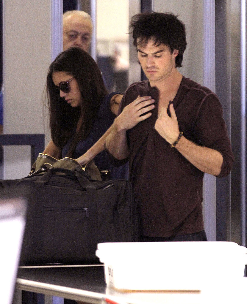 Ian Somerhalder adjust his shirt.