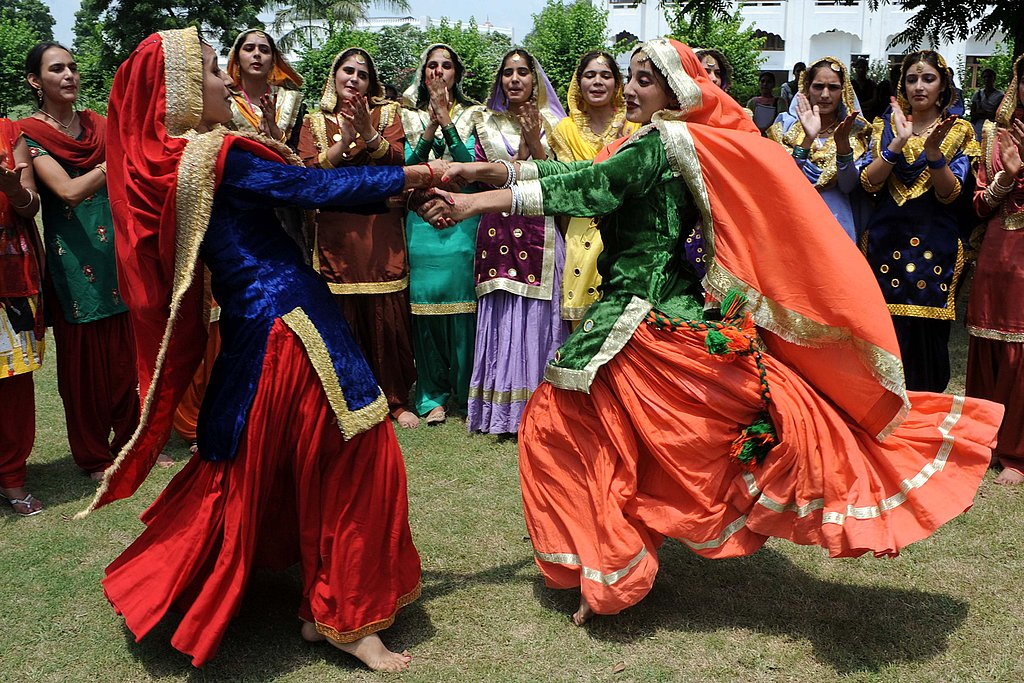 Indian girls dance in celebration for the Teej festival at Khalsa college for women in Amritsar.
