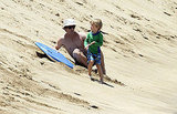 Danny Moder shirtless on the beach with son Henry.
