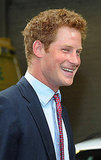 Prince Harry flashes a grin while meeting with emergency crew members.