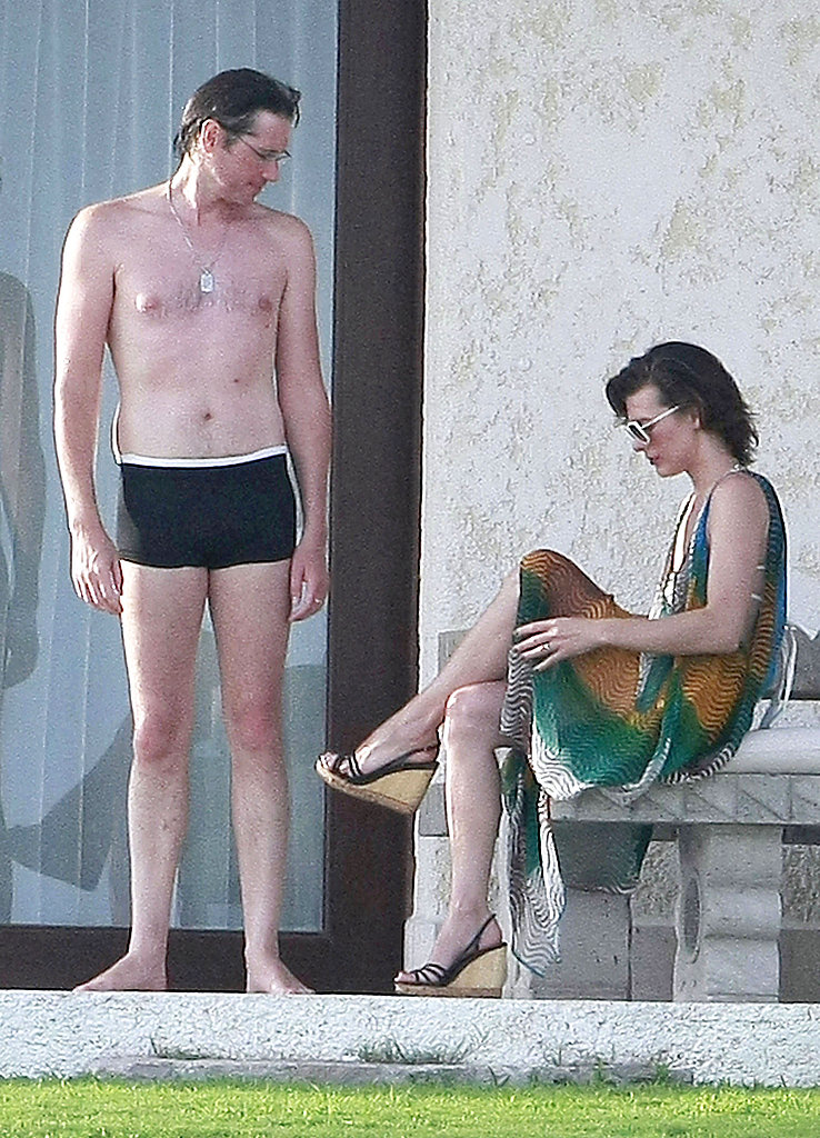 Paul W.S. Anderson wore short swim trunks with Milla Jovovich.