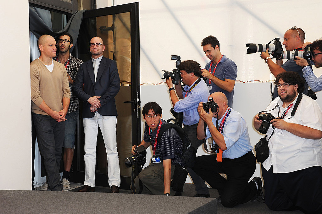 Matt Damon and Steven Soderbergh joke with photographers.