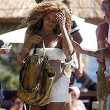 Beyoncé Knowles in a white bikini covers her baby bump.
