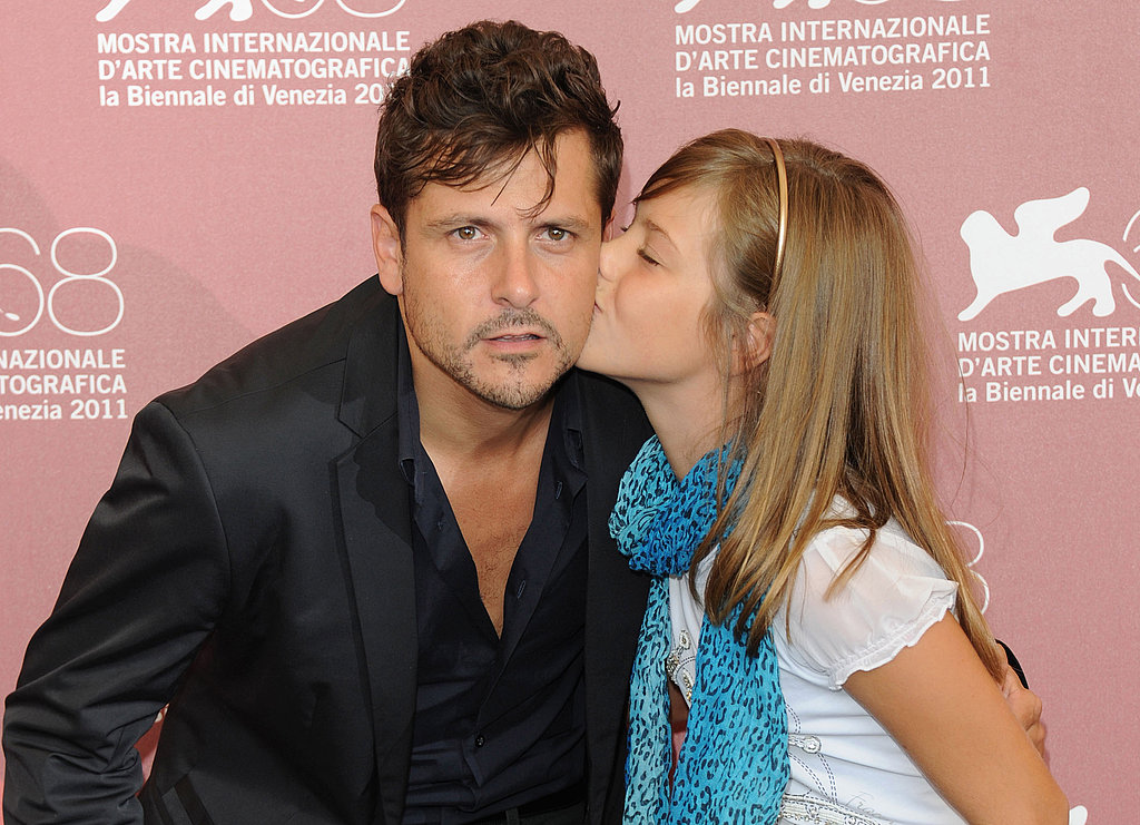 Actress Claudia Vega kisses her director, Kike Maillo, on the cheek at the Eva photocall.