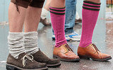 Gay revelers dressed with traditional Bavarian stockings stand outside Braeusrosl beer tent.