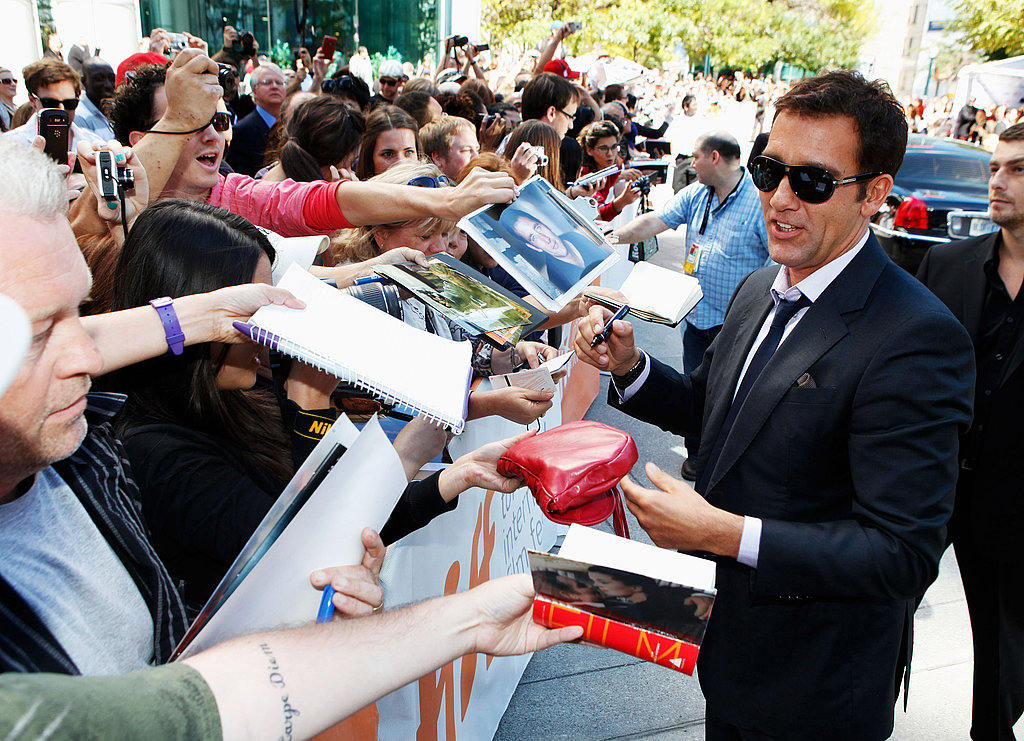 Clive Owen signs autographs for fans.