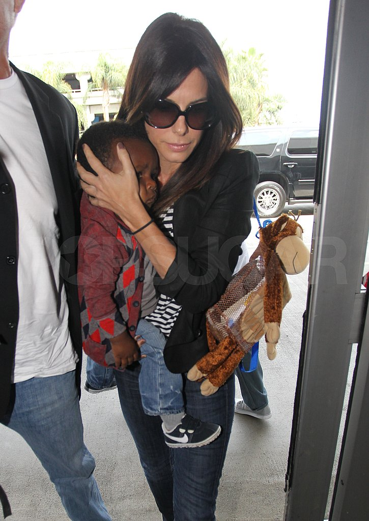 Sandra Bullock carried baby Louis and his toy monkey.