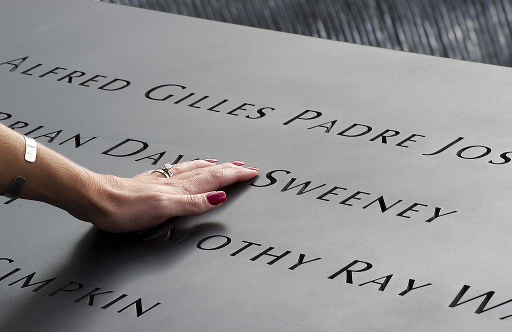 A woman places her hand on the memorial wall on the South Tower pool of the World Trade Center in NYC.
