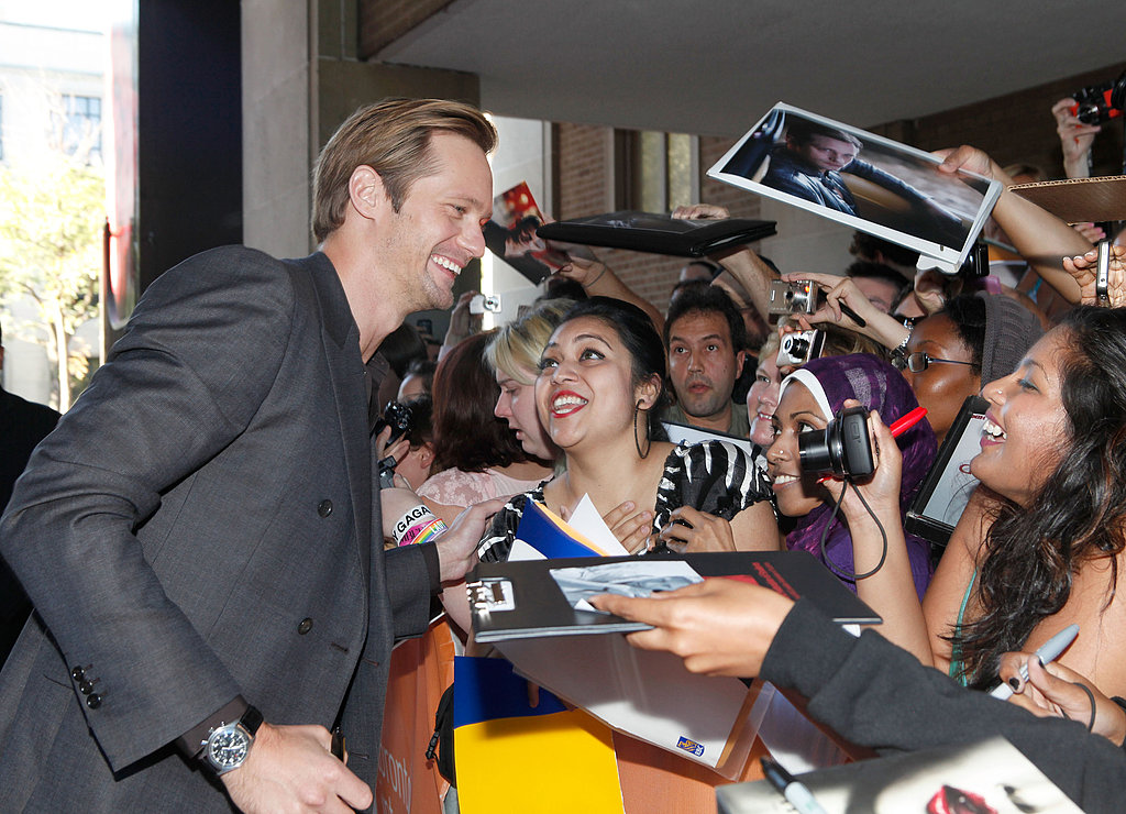Alexander Skarsgard flashes his pearly whites with his adoring fans at the Melancholia premiere during the Toronto International Film Festival.