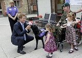 Prince Harry meets a serviceman with a spinal injury and his dog and two daughters during a visit to the charity Canine Partners Training Centre in 2010.