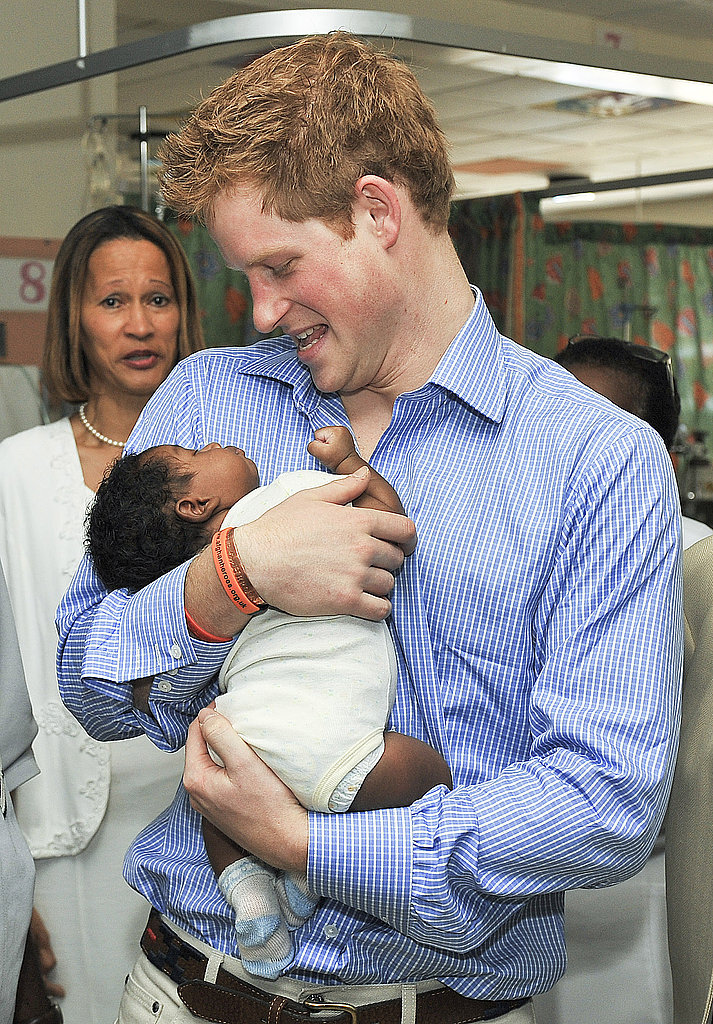 Harry holds a tiny baby during his visit to the children's ward at the Queen Elizabeth ll hospital in 2010.