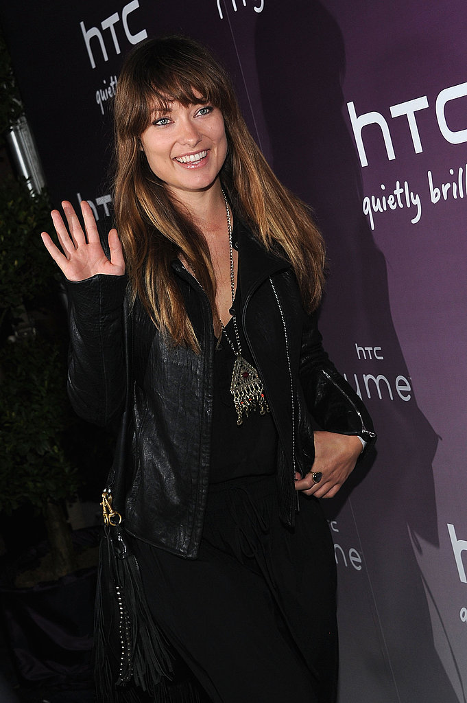 Olivia Wilde waves on her way into the launch party for the new HTC Rhyme Android smartphone.