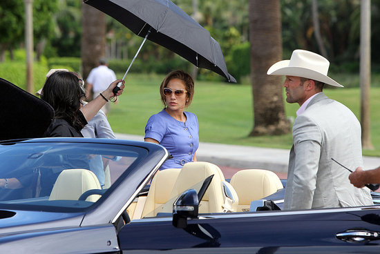 Jennifer was escorted to the set under a large umbrella.
