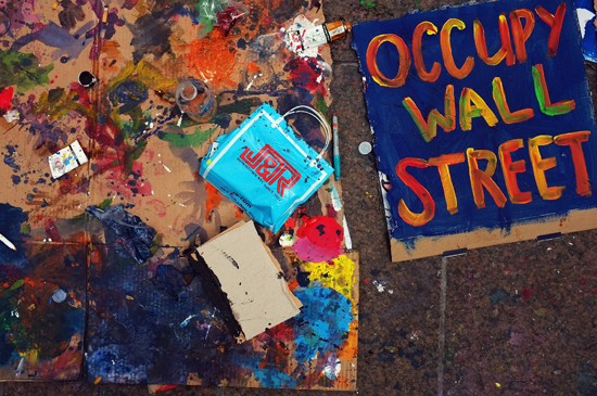 "An ""Occupy Wall Street"" sign lies on the ground."