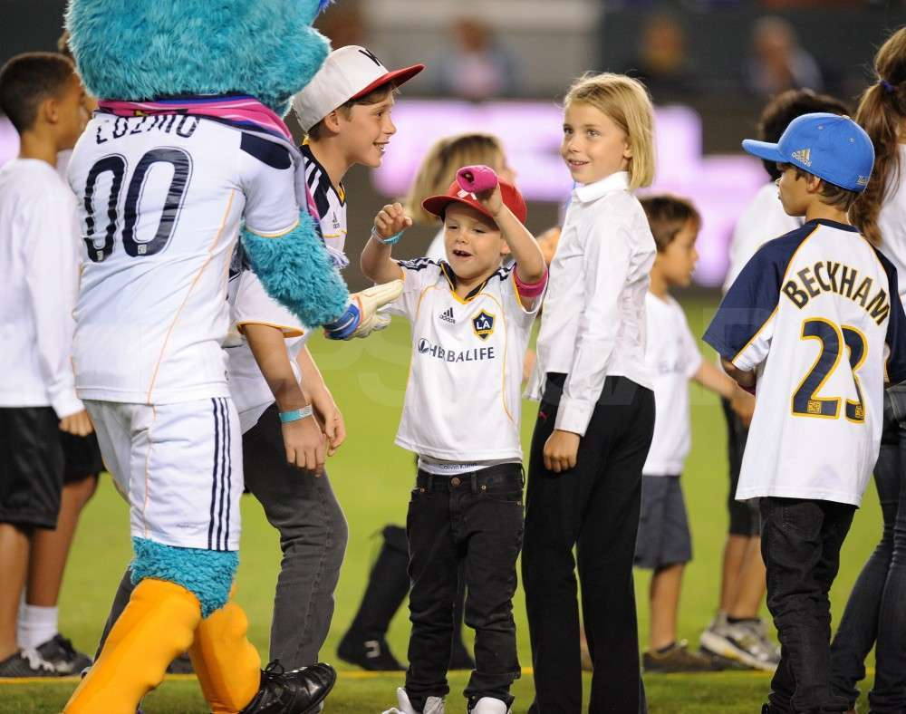 Cruz Beckham gave the team mascot a low ten as Brooklyn Beckham and Romeo Beckham hung out nearby.