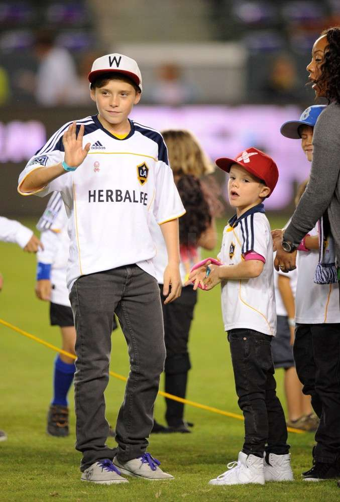 Brooklyn Beckham waved at a friend as Cruz Beckham and Romeo Beckham joined him on the field.