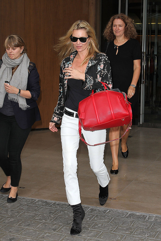 Kate Moss held a bright red bag.