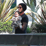 David Beckham carries daughter Harper Beckham.