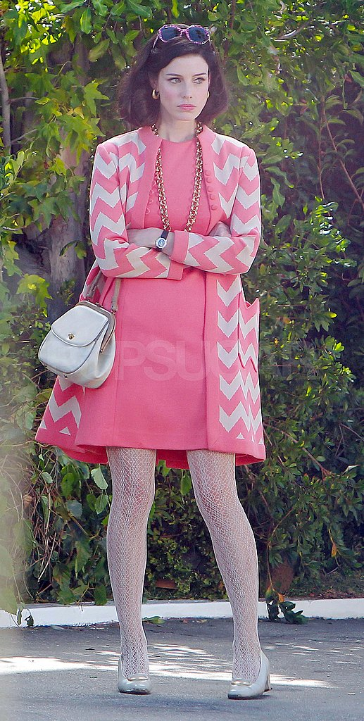 Jessica Paré in a pink dress and jacket on the set of Mad Men.