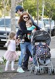 Isla Fisher maneuvers a stroller while out walking in Sydney with Sacha Baron Cohen, Elula Cohen, and Olive Cohen.