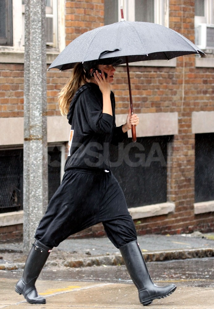 Gisele Bundchen stayed out of the rain with a large umbrella.