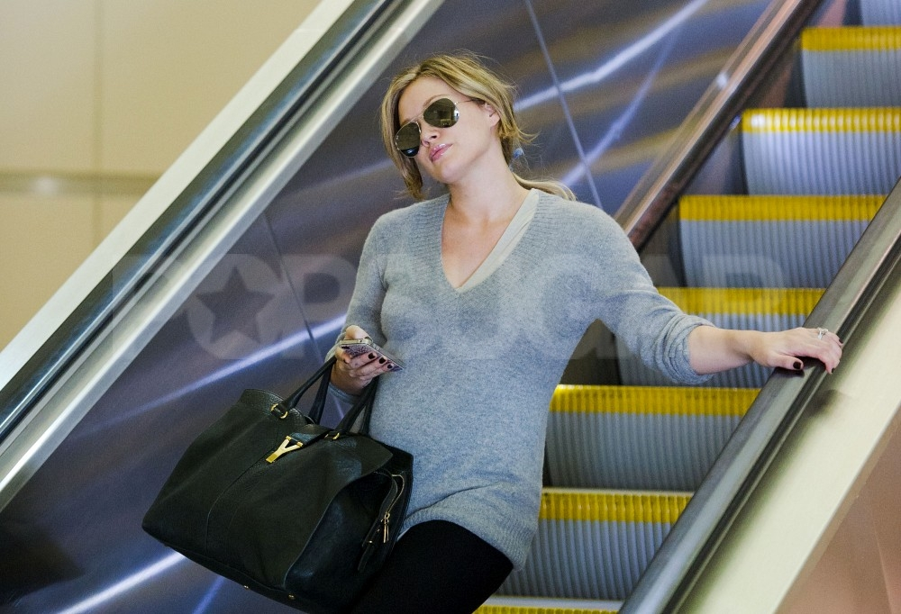 Pregnant Hilary Duff kept warm in a long gray sweater.