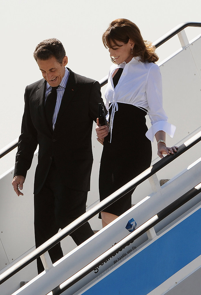 Carla Bruni stays close to her husband as they arrive for an official visit to Spain in 2009.