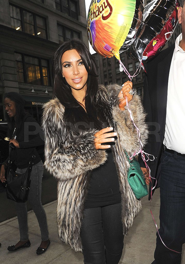 Kim Kardashian flashed a smile as she carried a mylar balloon.